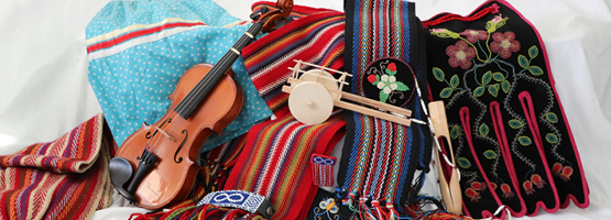 Still life of items tied to Metis culture: sashes, ribbon skirt, fiddle, traditional beadwork.